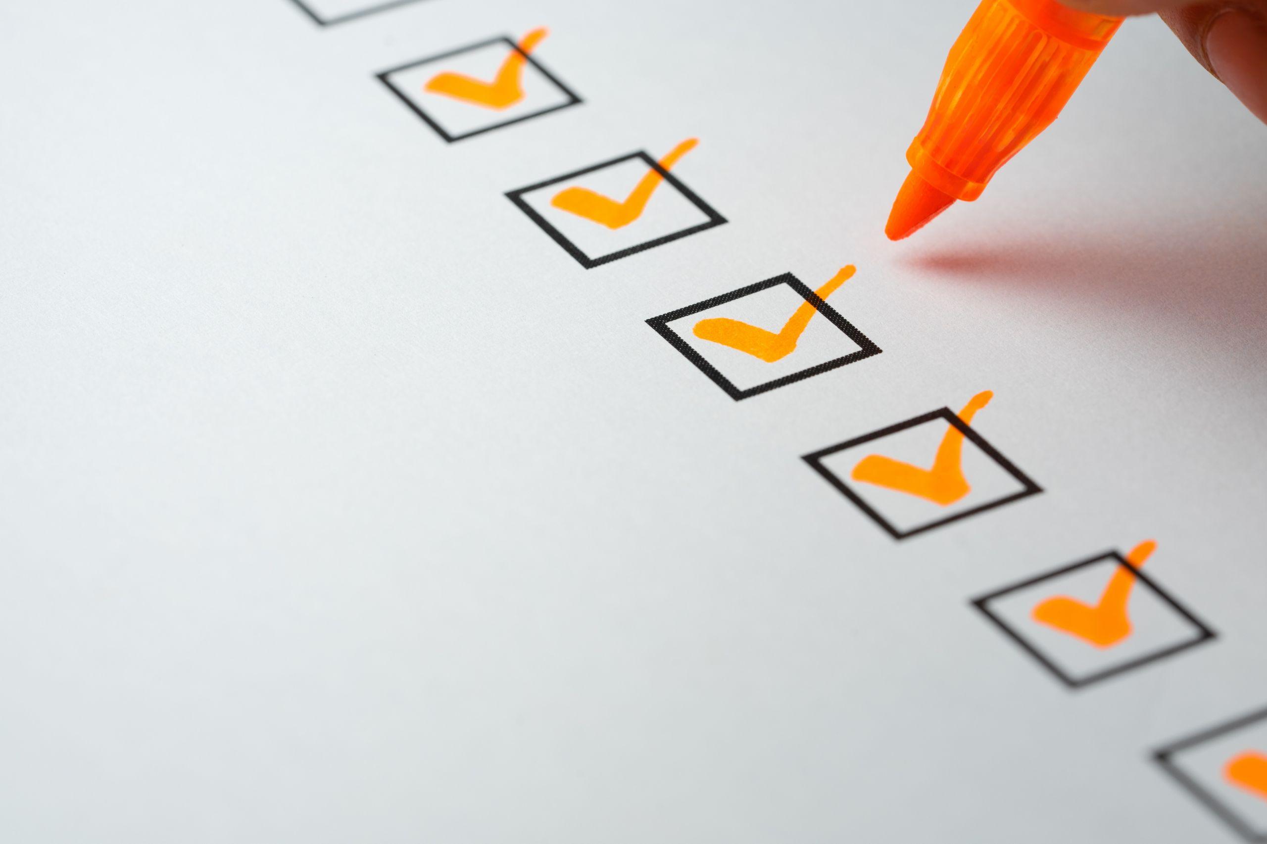 Eine Checkliste bestehend aus fünf Kästchen, die jeweils mit einem orangenem Haken versehen sind.