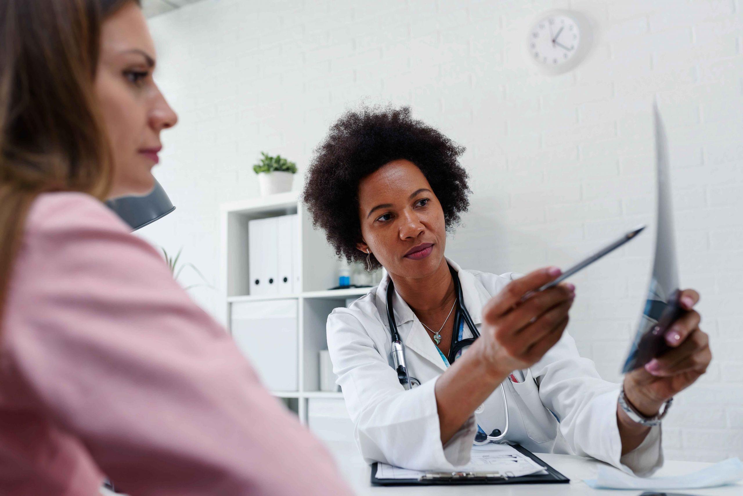 Zu sehen sind zwei Frauen, die sich am Tisch gegenüber sitzen. Die eine Frau ist Ärztin und zeigt der anderen Frau, die Patientin ist, was auf dem Röntgenbild in ihrer Hand zu sehen ist.